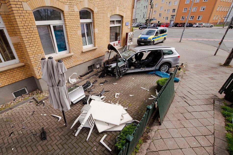 Der VW-Passat steht vollkommen zerstört vor einer Hauswand.