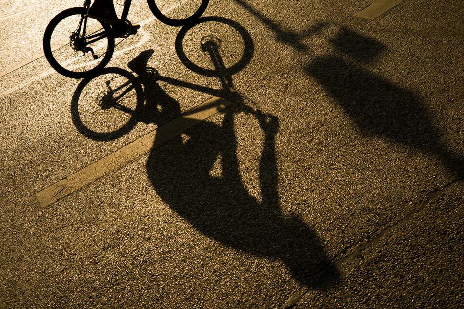 Der Schatten eines Radfahrers zeichnet sich in Licht der Abendsonne auf dem Asphalt einer Strasse in der Innenstadt ab.