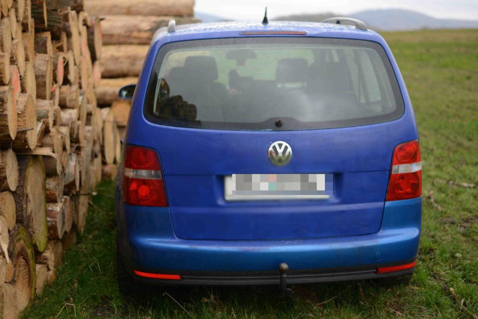 Der VW Touran steht auf dem Feld.