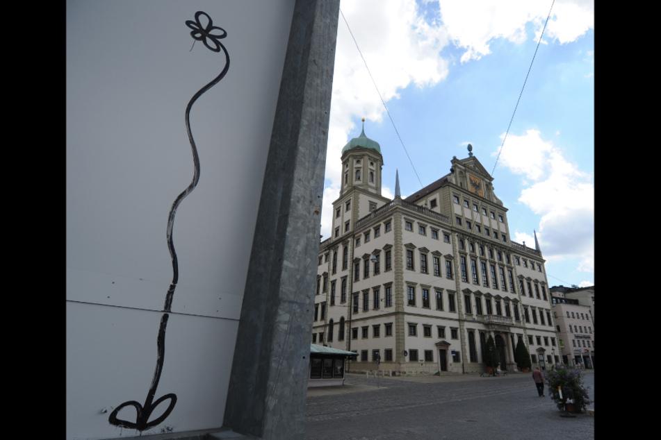 Neben dem Rathaus von Augsburg ist eine Graffiti-Blume zu sehen. Die Augsburgblume wurde überregional bekannt. Der Graffitikünstler muss sich nun am 19.11.2020 erneut wegen Sachbeschädigung durch Graffitis vor Gericht verantworten.