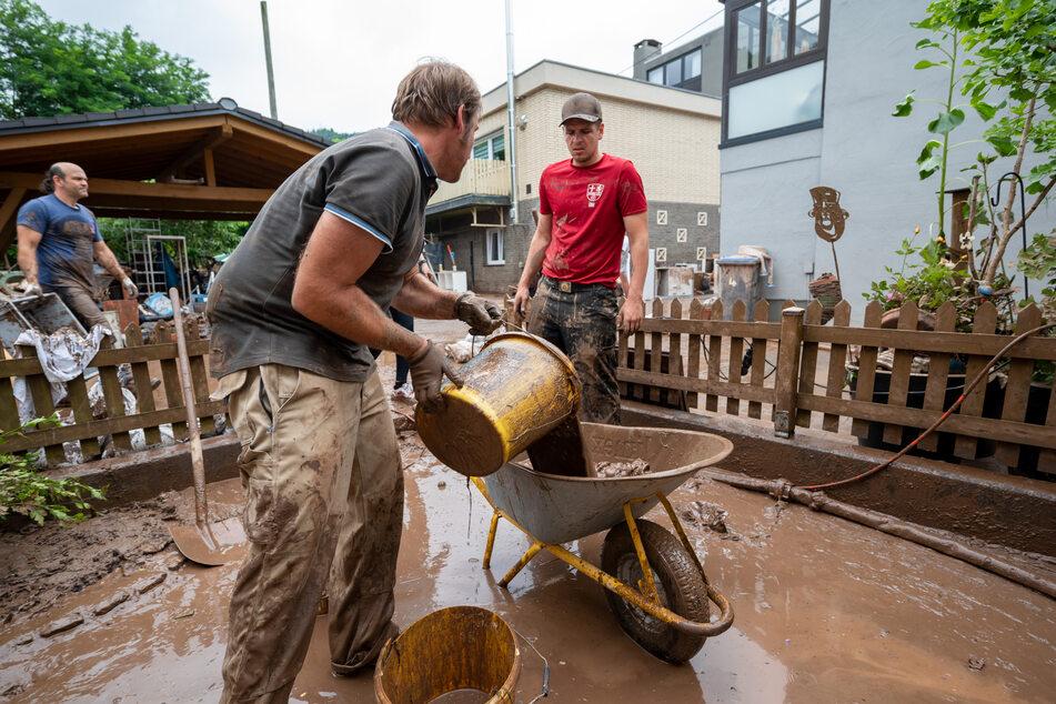 Rheinland-Pfalz, Kordel: Mit Eimern und Schubkarre entsorgen Anwohner die Schlammmassen nach dem Hochwasser der Kyll. Zahlreiche Häuser im Ort waren betroffen, Bewohner mussten evakuiert werden.
