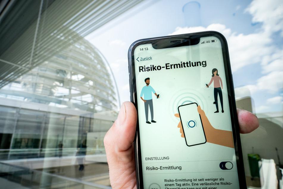 Die Corona-Warn-App mit der Seite zur Risiko-Ermittlung ist im Display eines Smartphone vor der Kuppel des Reichstags zu sehen.