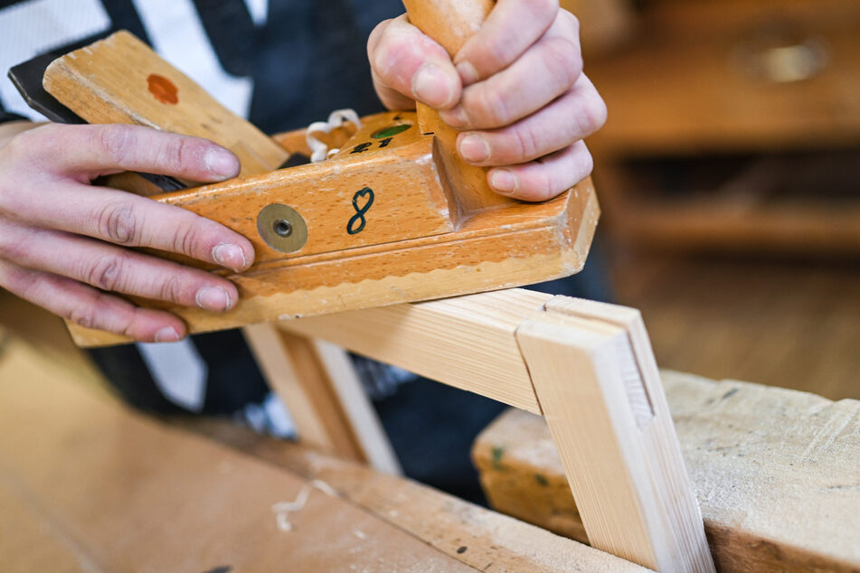 Ein Auszubildender im Schreiner-Handwerk arbeitet an einem Werkstück (Archivbild).