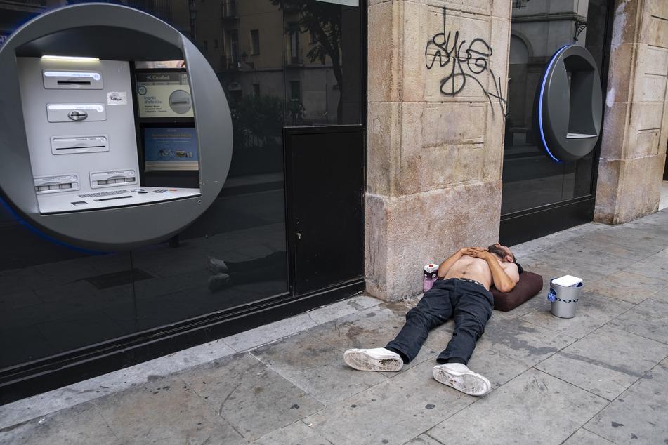 Ein obdachloser Mann schläft auf der Straße neben einem Geldautomaten.