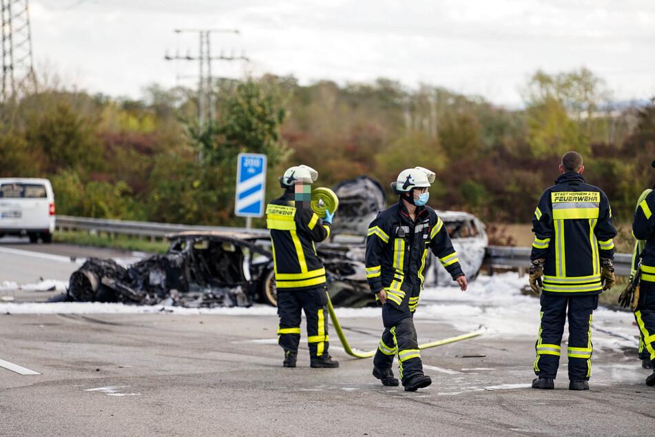 Einsatzkräfte der Feuerwehr Hofheim am Taunus stehen vor dem völlig ausgebrannten Lamborghini.