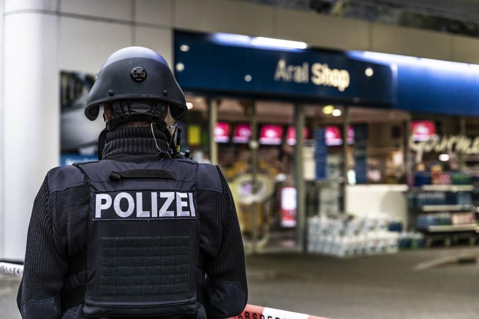 Ein Polizist sichert die Tankstelle, an der sich die grausame Tat ereignet hatte.