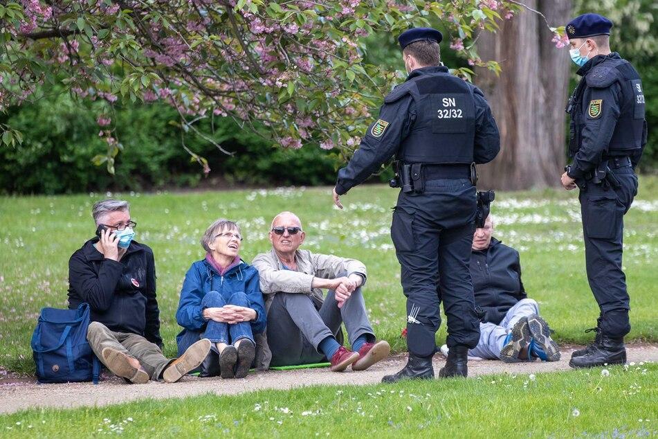 Zwei Beamte kontrollieren vier Personen, die im Großen Garten auf dem Boden sitzen.