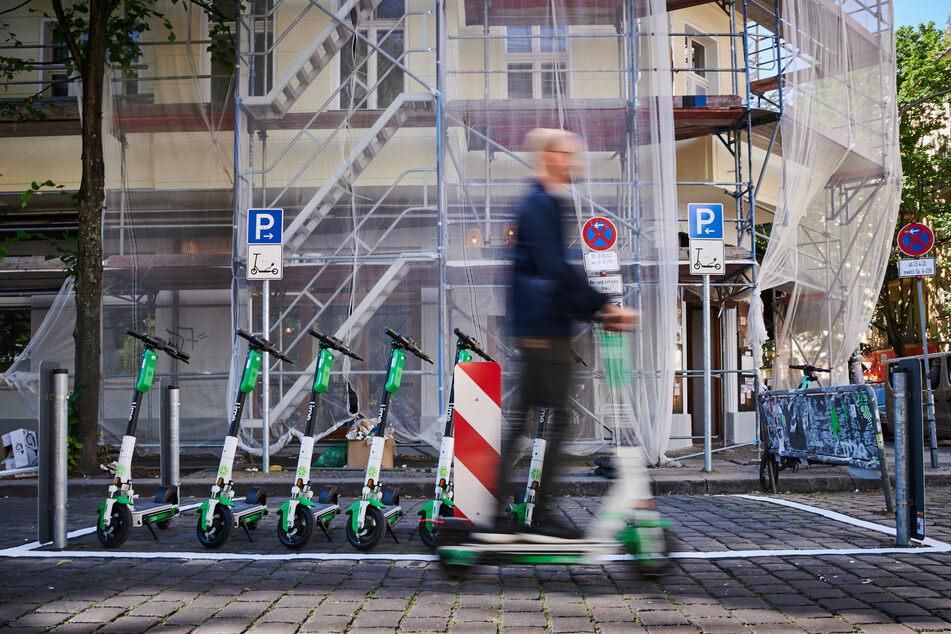 Ein Mann auf einem E-Scooter fährt an einem E-Scooter-Stellplatz in Berlin vorbei.