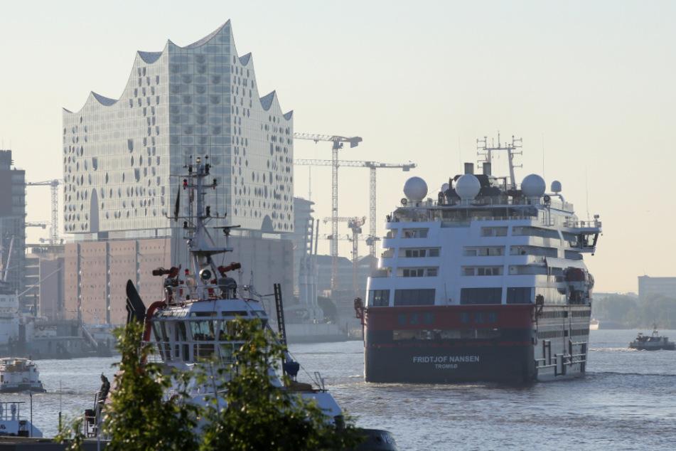 """Das Hurtigruten-Schiff """"Fridtjof Nansen"""" läuft am Morgen in den Hafen von Hamburg ein und fährt an der Elbphilharmonie entlang."""