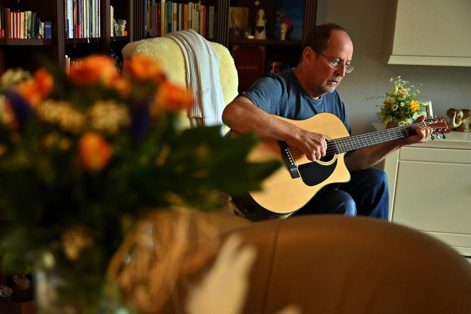 Roman Bialas sitzt in seinem Wohnzimmer und spielt auf der Gitarre. Es ist ein halbes Jahr her, dass er schwer an Covid-19 erkrankt ist.