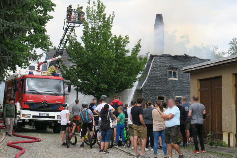 Mehrere Menschen sehen den Rettungskräften bei der Arbeit zu.