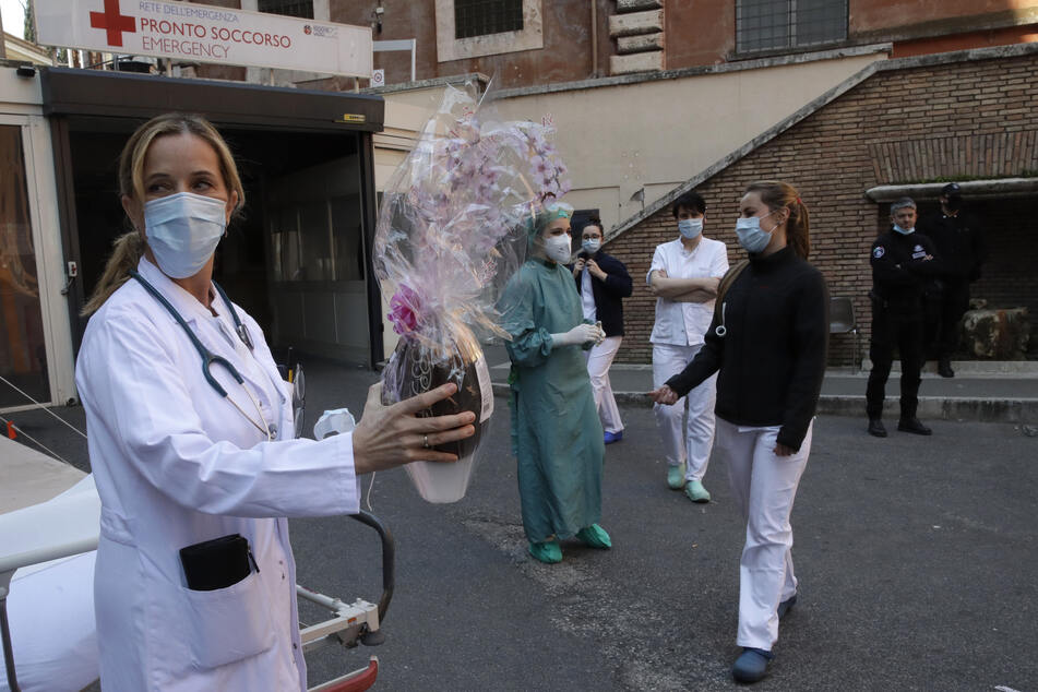 Monica Carfora, stellvertretende Leiterin der Notaufnahme des Krankenhauses Santo Spirito in Rom, hält ein Osterei aus Schokolade in der Hand, während sie mit ihrem Team eine Pause für eine kleine Osterfeier vor dem Eingang des Notfallzentrums einlegt.