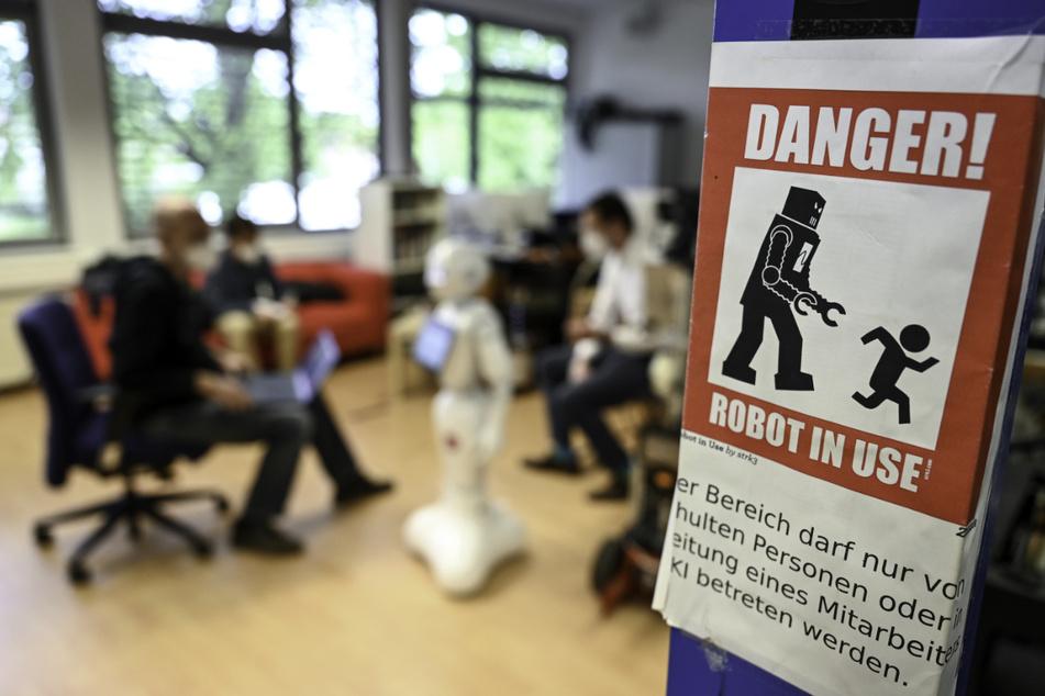"""Ein Warnschild mit der Aufschrift """"Danger! Robot in use"""" (dt. """"Gefahr! Roboter in Betrieb"""") hängt an einem Pfeiler."""