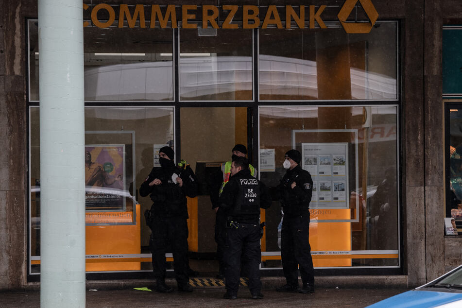Polizisten stehen nach dem Überfall am Eingang einer Bankfiliale an der Blissestraße in Wilmersdorf.