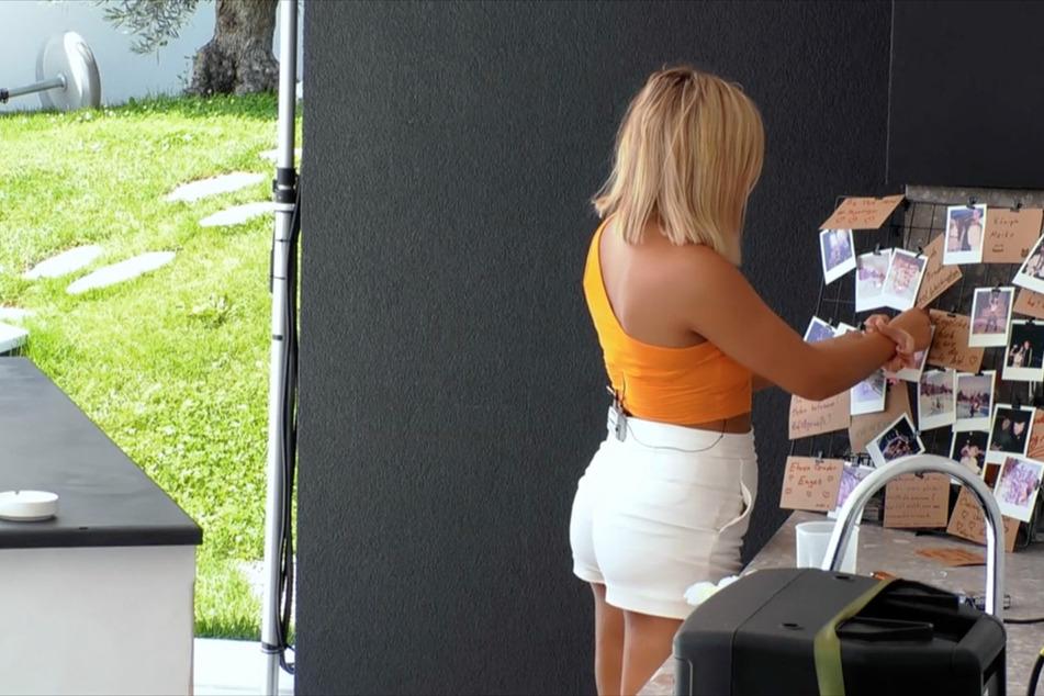 """Verführerin Gina (23) nimmt ihr Glück bei """"Temptation Island"""" selbst in die Hand und rupft die Bilder von Mikes (28) Freundin Sabine (28) von der Fotowand."""