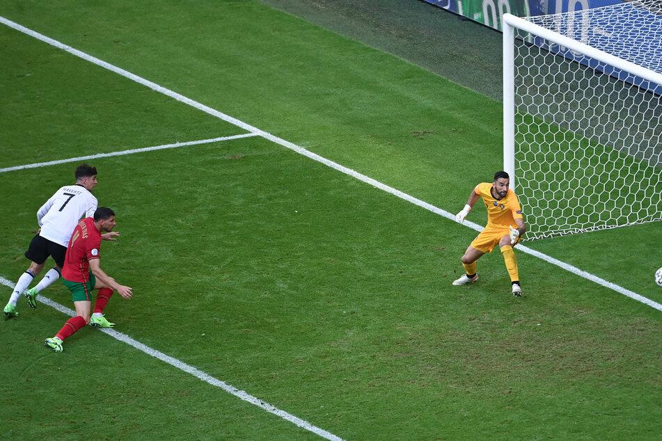 Ruben Dias (M.) gleicht - von Havertz (l.) bedrängt - zum 1:1 für Deutschland aus. Rui Patricio ist chancenlos.