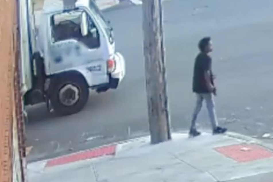 A still from surveillance footage, showing the 13-year-old suspect carrying a gun.