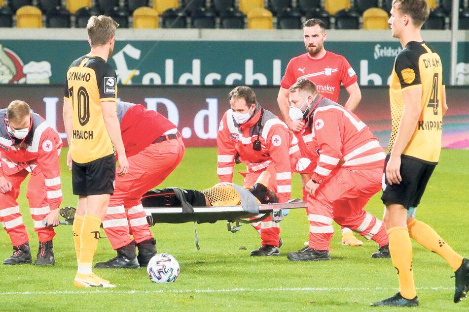 Der verletzte Chris Löwe wird auf einer Trage abtransportiert, Tim Knipping (r.) und sein Teamkollege Patrick Weihrauch sind fassungslos.