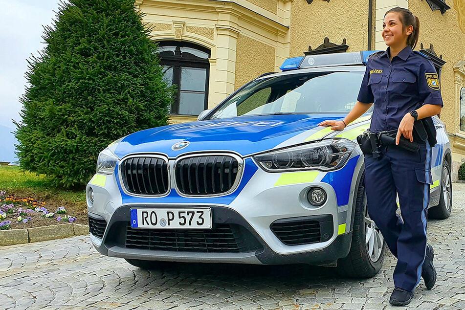 Melanie Hochreiter (23), Snowboarderin und Polizistin, steht lächelnd neben einem Dienstfahrzeug der Polizei.