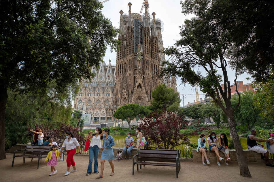 """Passanten stehen in einem Park der """"Sagrada Familia"""". Die weltberühmte Basilika ist nach 114 Tagen Zwangsschließung während der Corona-Krise wieder für die Öffentlichkeit zugänglich."""