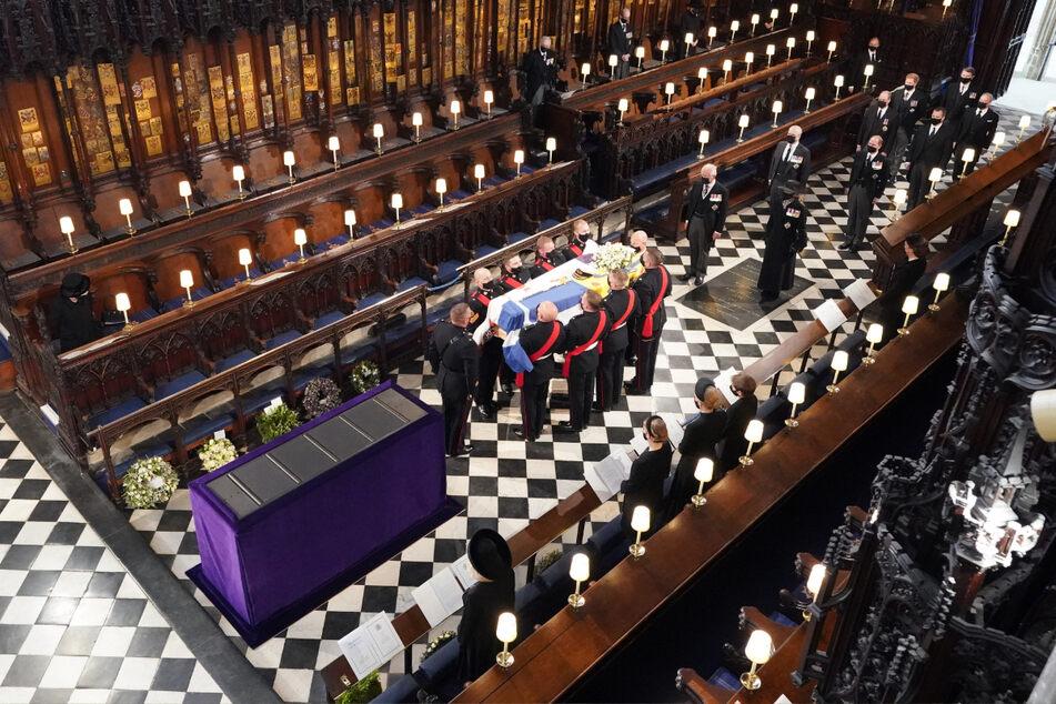 Königin Elizabeth II. (l.) verfolgt in der St.-Georgs-Kapelle, wie Sargträger den Sarg von Prinz Philip in die St.-Georgs-Kapelle auf Schloss Windsor tragen.