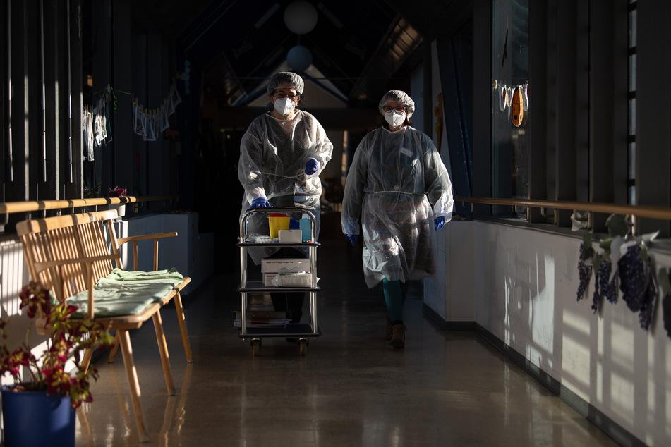 Zwei Altenpflegerinnen gehen in einem Seniorenheim mit Schutzausrüstung, die sie für die Durchführung von Antigen-Schnelltest angelegt haben, durch einen Gang.