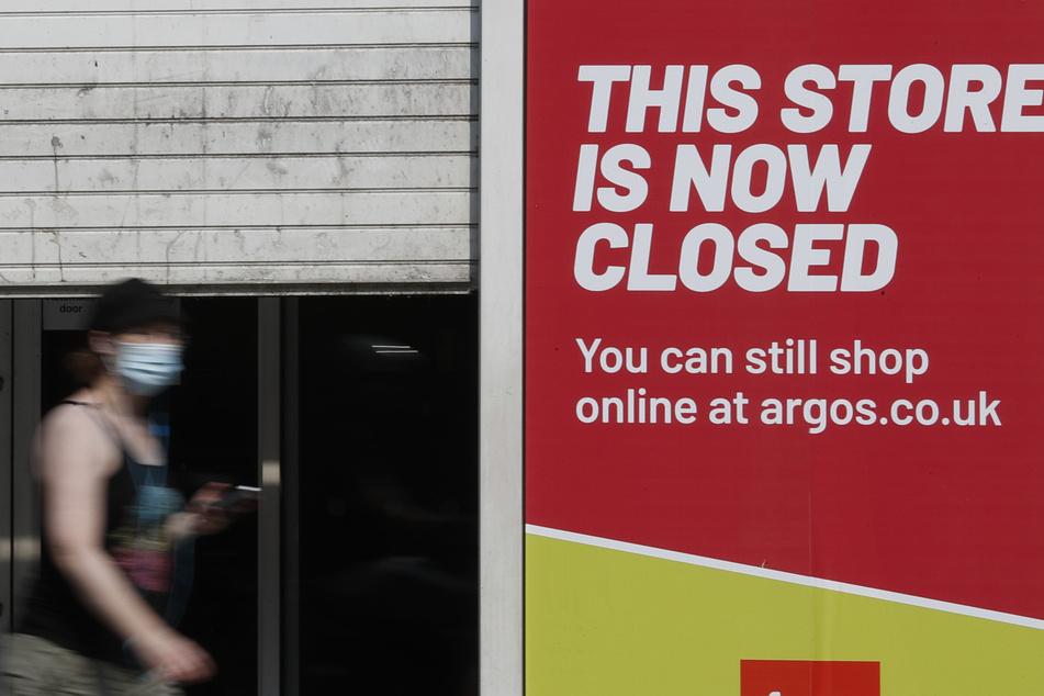 Eine Passantin mit Mundschutz geht an einem geschlossenen Geschäft vorbei.