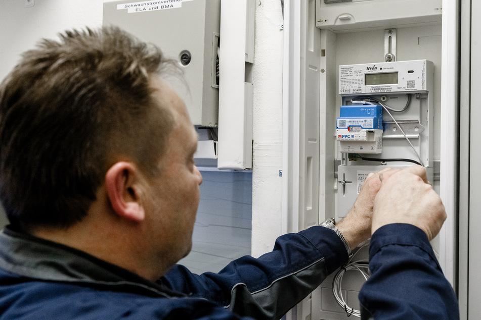 Ein Elektriker arbeitet an einem digitalen Stromzähler.