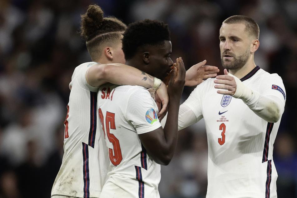 Englands Kalvin Phillips, (l.) und Luke Shaw, (r.), trösten ihren Mannschaftskameraden Bukayo Saka, nachdem dieser beim Elfmeterschießen einen Elfmeter nicht verwandeln konnte.