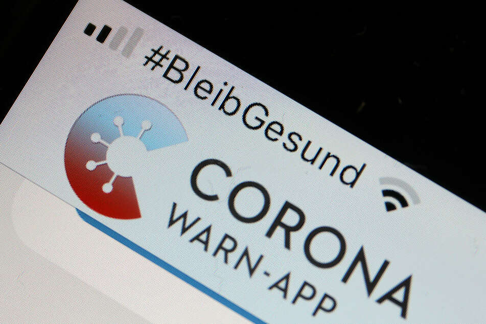 """Die offizielle Corona-Warn-App ist auf einem Smartphone zu sehen, darüber steht der Hashtag """"#BleibGesund""""."""
