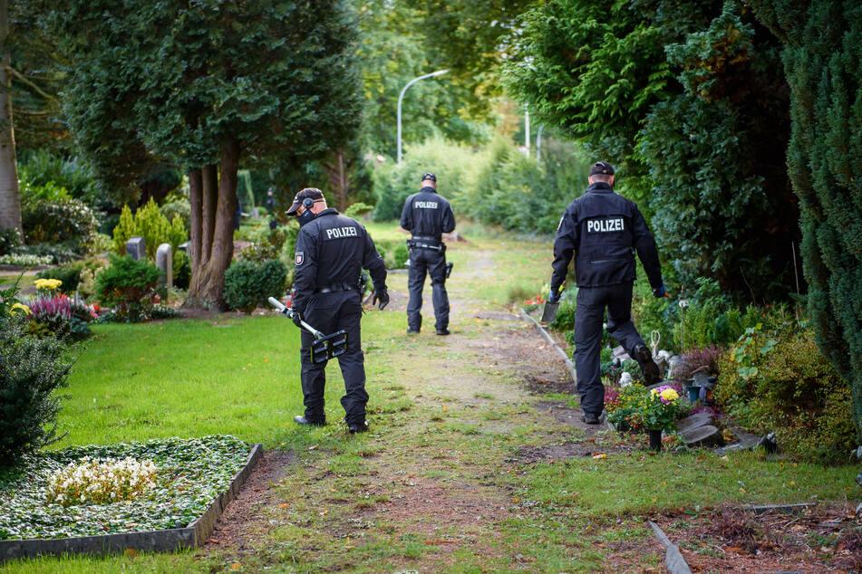 Mit einem Metalldetektor sucht die Polizei den Rendsburger Friedhof ab.