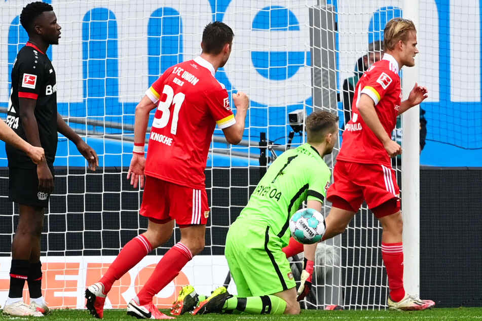 Nix zu halten für Leverkusens Keeper Lukas Hradecky (M). Unions Stürmer Joel Pohjanpalo (r.) bejubelt mit Robin Knoche (l.) sein Tor zum 1:1.