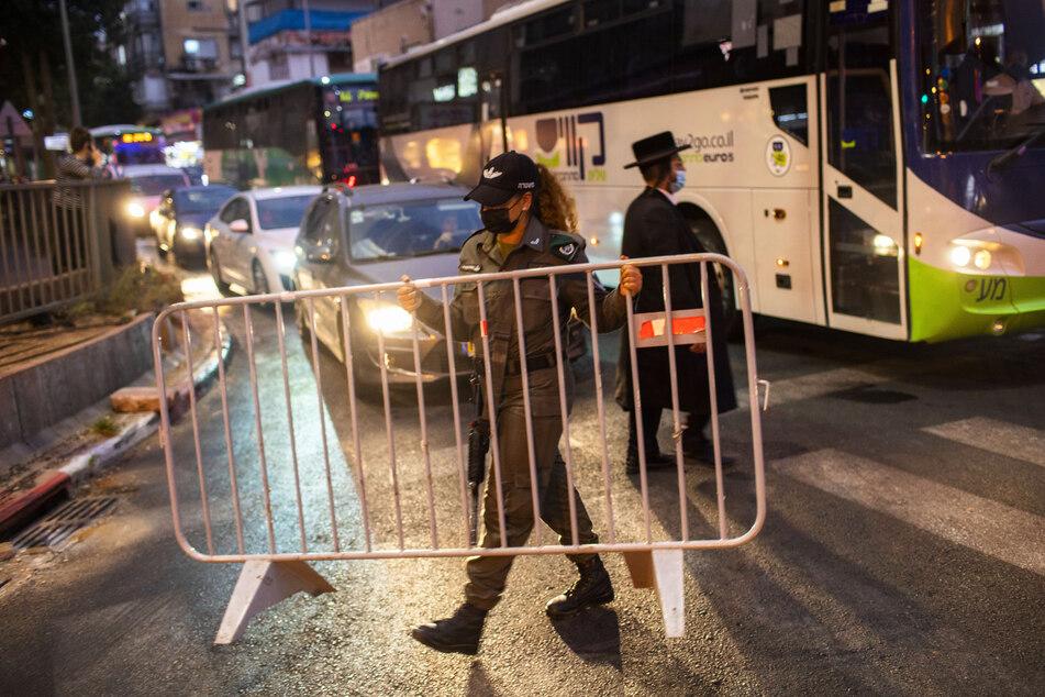 Ein israelischer Grenzpolizist errichtet in der ultra-orthodoxen jüdischen Stadt Bnei Brak vor einer nächtlichen Ausgangssperre auf einer Hauptstraße eine Absperrung. Israel hat die Maßnahmen für 40 israelische Städte und Ortschaften mit besorgniserregenden Corona-Fallzahlen verschärft, nächtliche Ausgangssperren verhängt und Schulen geschlossen.