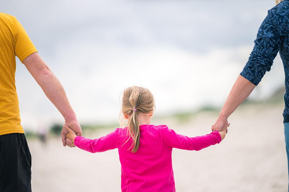 Ein junges Mädchen geht händchenhaltend zwischen ihren Eltern am Badestrand von Norddeich entlang.
