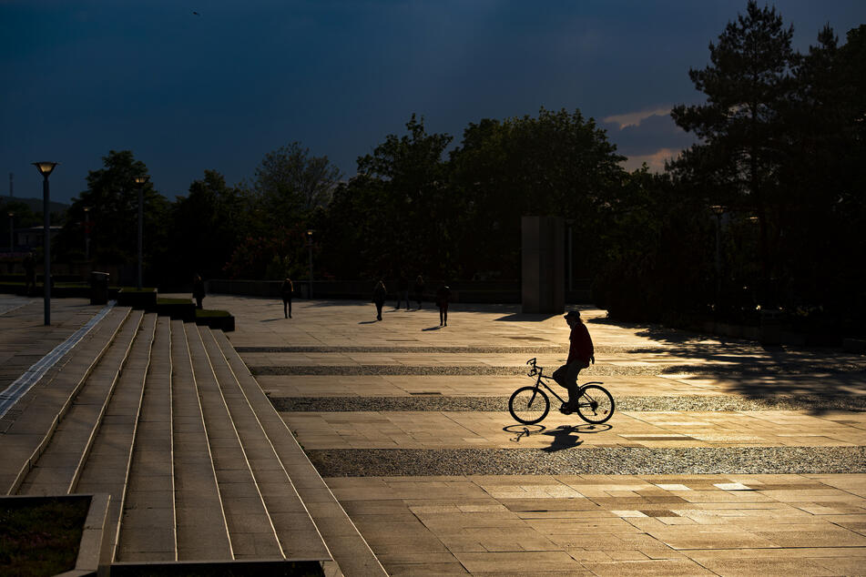 Ein Mann fährt während der Coronavirus-Pandemie mit Mundschutz auf einem Fahrrad in Prag.