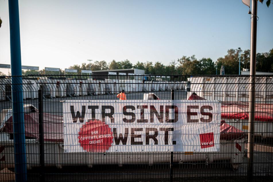 """Auf einem Banner an einem Zaun des Wertstoffhof steht bei einem Warnstreik im öffentlichen Dienst """"Wir sind es wert"""". Die Wirtschaftsbetriebe in Duisburg bestreiken den Recyclinghof Duisburg-Nord."""