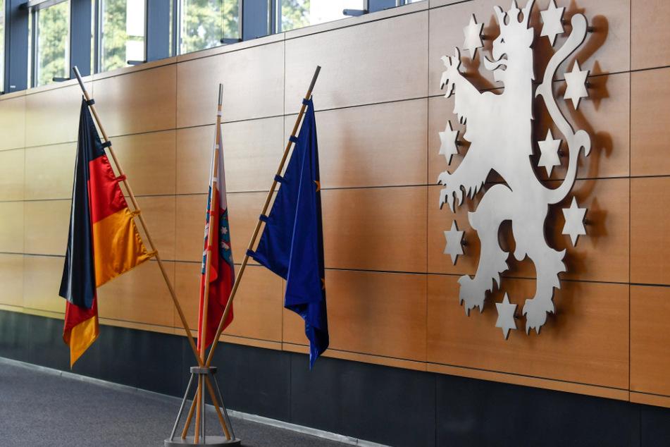 Die Deutschlandfahne, die Fahne der EU und die Fahne von Thüringen, stehen im Thüringer Landtag vor dem Wappen des Landes: Im April soll eigentlich ein neuer Landtag gewählt werden.