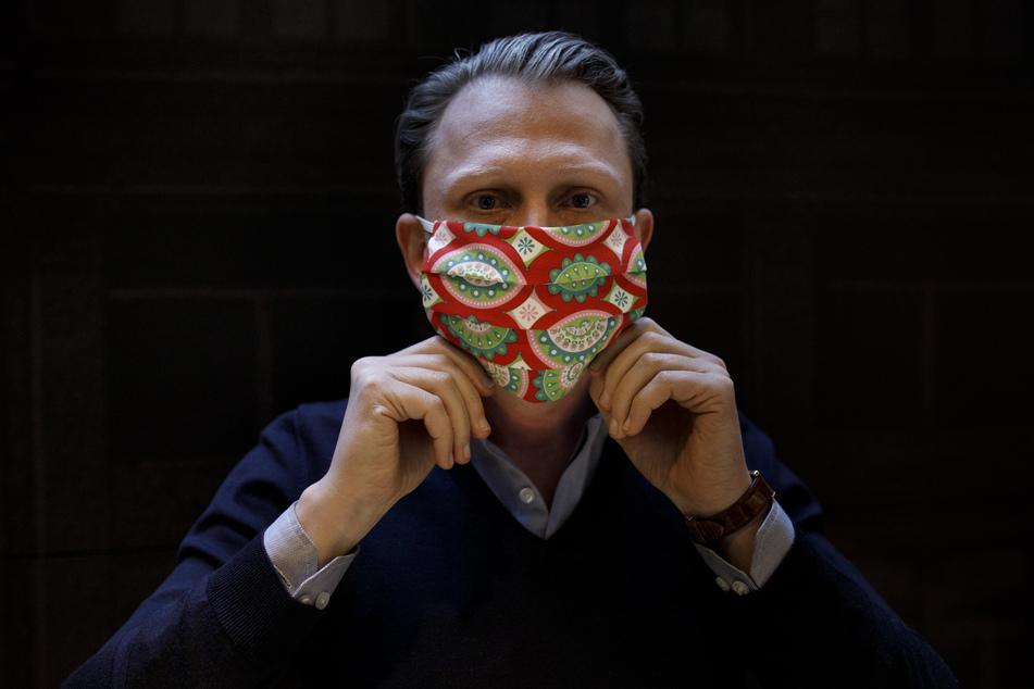 Jan Scheper-Stuke, Geschäftsführer der Berliner Krawattenmanufaktur Auerbach, zeigt in der Krawattenwerkstatt eine bunte Mund-Nase-Maske aus Stoff. Seit der vergangenen Woche werden verschiedene Modelle von Mund-Nase-Masken aus verschiedenen Stoffen von dem Krawattenhersteller angeboten.