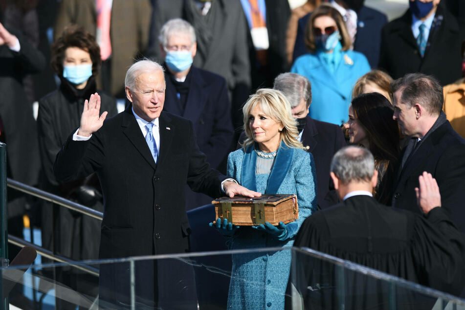 President Joe Biden reciting the oath of office, while Dr. Jill Biden holds the family Bible.