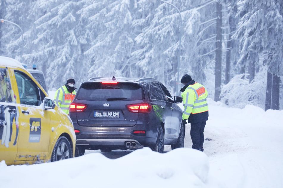 Polizeibeamte stehen an einer Zufahrtsstraße zum Grenzadler und kontrollieren Fahrzeuge. Oberhof riegelt sich vor Tagestouristen ab.