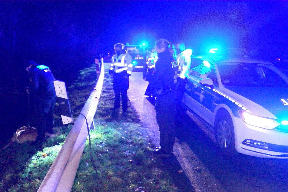 Einsatzkräfte der Polizei suchen mit Spürhunden den Bereich um den Unfallort ab, um den flüchtigen Fahrer zu finden.