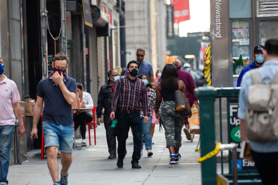 New York: Fußgänger gehen mit Mund-Nasen-Bedeckungen am Broadway . Seit Beginn der Pandemie sind in den USA mehr als sieben Millionen Covid-19-Infektionen verzeichnet worden.