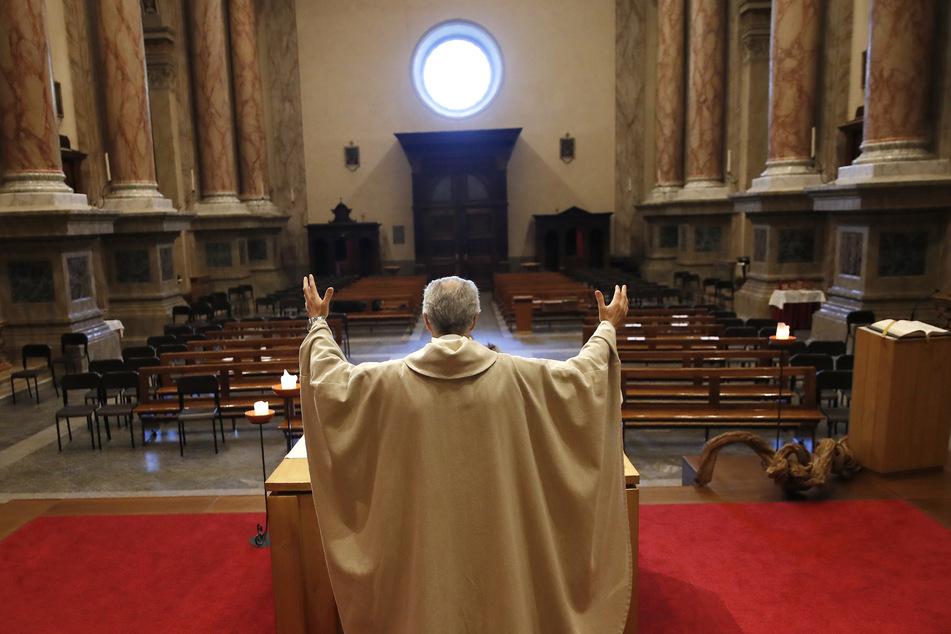 Priester Don Angelo Riva hebt seine Hände zur Segnung während er eine Messe in einer leeren Kirche abhält. In Italien gelten auch weiterhin strenge Ausgangsbeschränkungen, um die Ausbreitungdes Coronavirus einzudämmen.