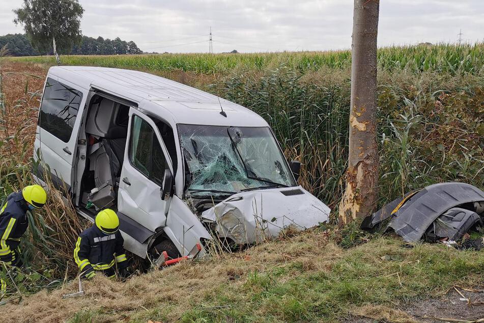 Rettungskräfte stehen am Wrack des Kleintransporters.