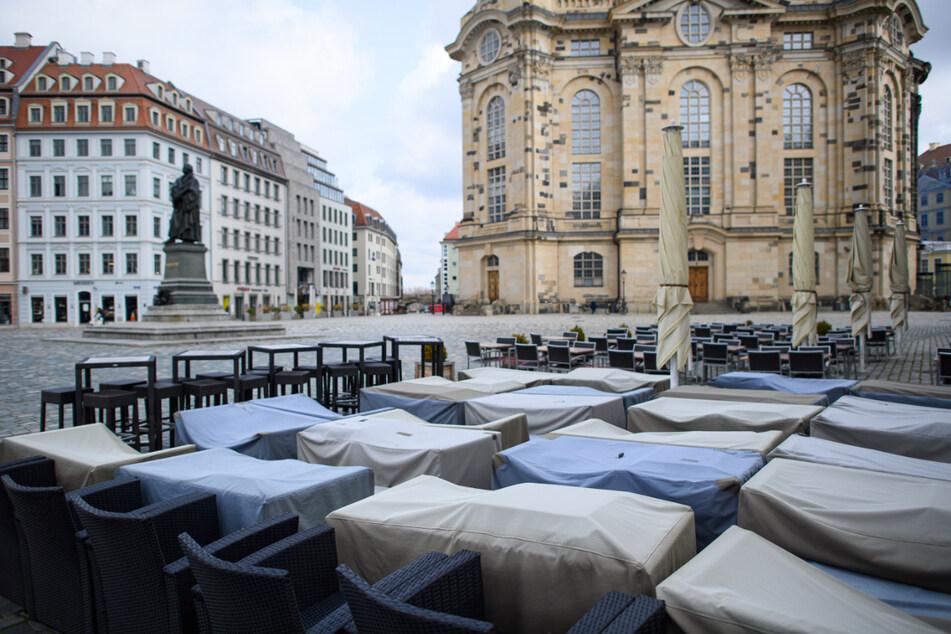 Sitzgelegenheiten eines Restaurants auf dem Neumarkt vor der Frauenkirche sind mit Schutzbezügen umhüllt.