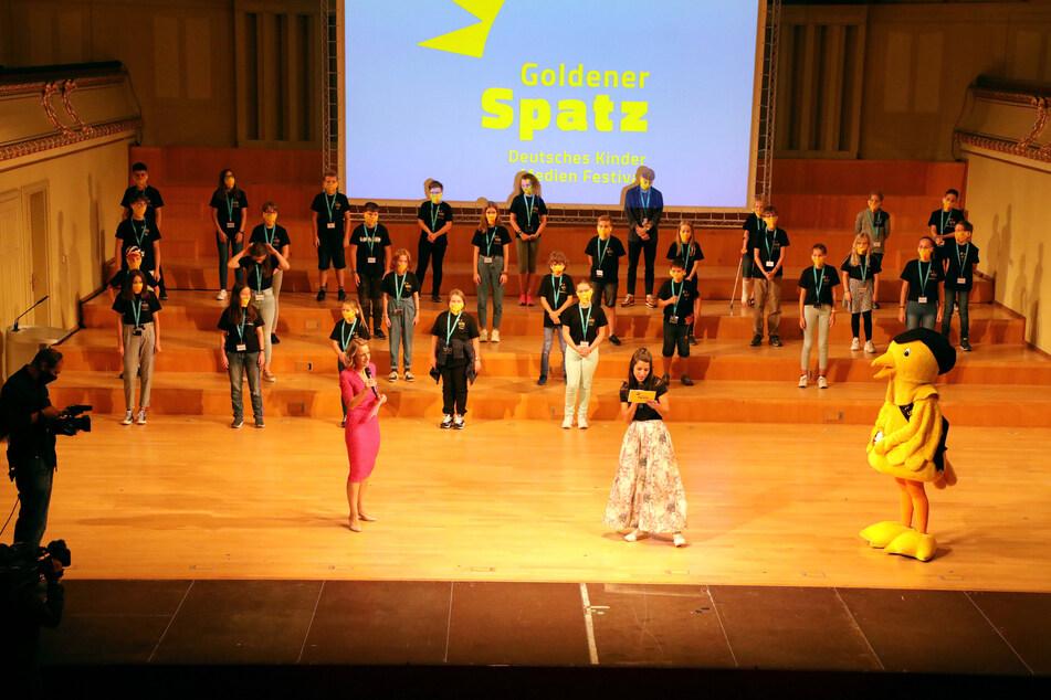 Sie schaut sich das gesamte Wettbewerbsprogramm an: Die Kinderjury auf einer Bühne mit Festivalleiterin Nicola Jones (45, in pink), KiKA-Moderatorin Clarissa Correa da Silva (29, im langen Rock) und dem Maskottchen.
