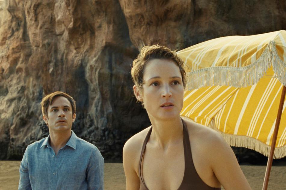Guy (42, Gael Garcia Bernal, l.) und Prisca (37, Vicky Krieps) sind schockiert: Der Strand ist nämlich alles, nur nicht friedvoll!