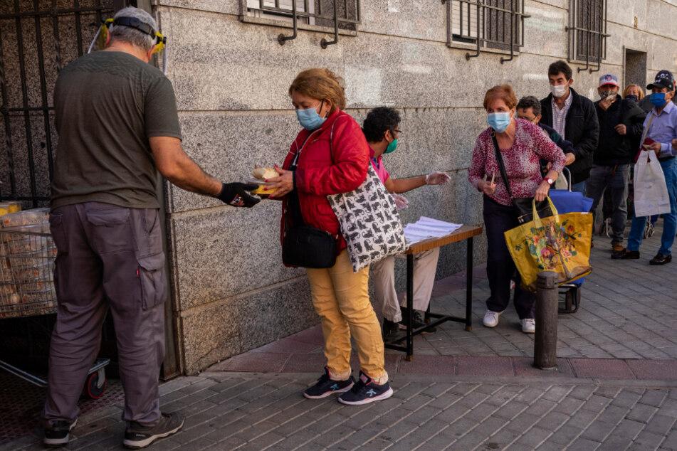 Madrid: Menschen stehen Schlange vor dem Sitz eines katholischen Ordens inmitten der Corona-Pandemie, weil dort Freiwillige Lebensmittel verteilen.
