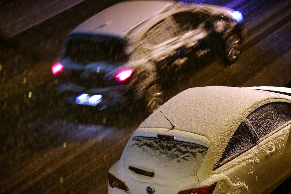 Autos fahren durch das Schneetreiben in Würzburg.