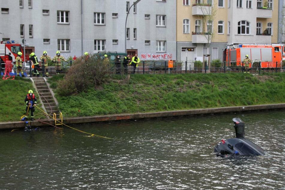 Einsatzkräfte versuchen, an das Auto im Neuköllner Schifffahrtskanal heranzukommen.
